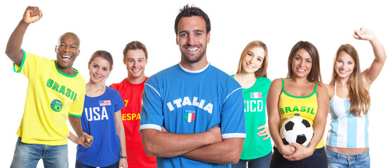 Italian soccer fan with crossed arms and other fans