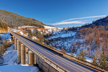 mountain bridge in winter with snow and blue sky