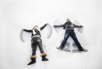 boy and girl making snow angels