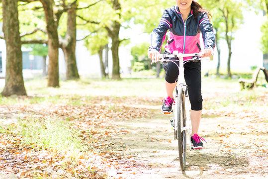 自転車に乗って森の中をサイクリングする日本人女性