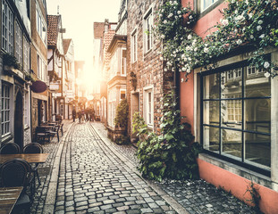 Fototapeta Historic street in Europe at sunset with retro vintage effect