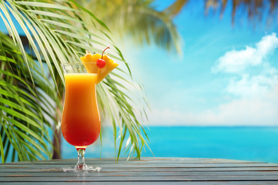 Refreshing orange cocktail on beach table.