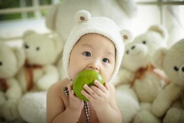 Baby eating green apple