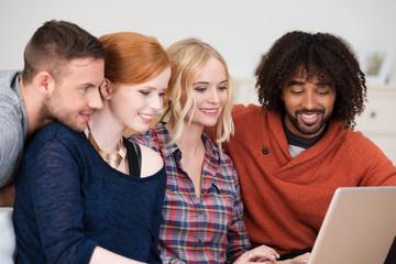 lachende freunde schauen zusammen auf laptop