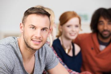 lächelnder junger mann mit seinen freunden