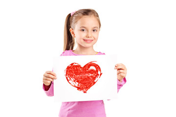 Cute little girl holding a painting of a red heart