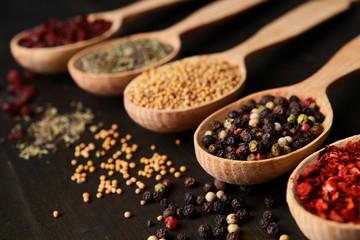 Foto auf AluDibond Gewürze 2 Different spices in spoons on wooden background