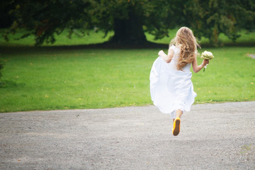 Young girl is runnig away in white dress