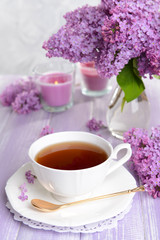 Beautiful lilac flowers with cup of tea