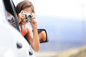 Woman tourist taking photo in car with camera