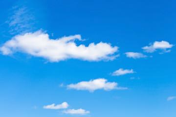 few little fluffy white clouds in blue sky