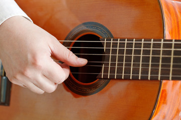 male hand plays on acoustic guitar
