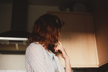 Young woman standing in her kitchen and thinking