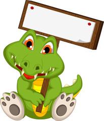 cute baby crocodile holding blank board