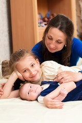 Mom hugs baby and older daughter at home