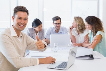Casual business team having a meeting with man giving thumbs up