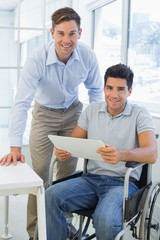 Casual businessman in wheelchair smiling at camera with colleagu