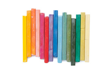 stack of oil pastels organized like a rainbow