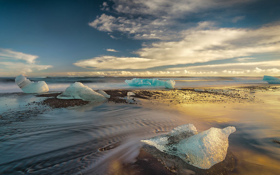 Melting Icebergs on the Shore at Sunset