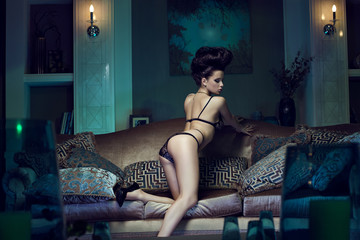 Girl in lingerie and stylish hairstyle on the couch