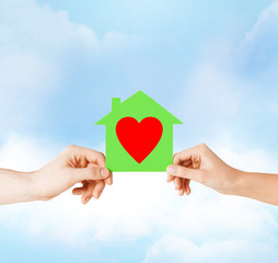 couple hands holding green paper house