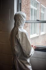 Scientist in boiler suit by window