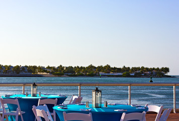 Fototapete - Dining tables overlooking ocean waters at sunset.