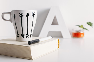 White coffee mug with arrows and diy decoration.
