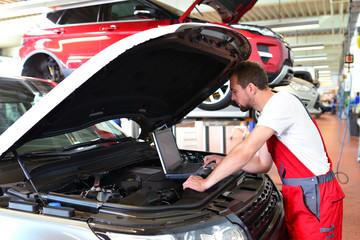 KFZ Mechaniker mit Diagnosegerät am Motor eines Fahrzeuges