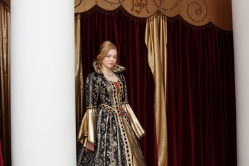 Actress in royal dress posing on curtain backdrop Wall mural