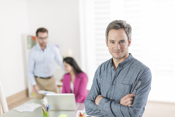 senior businessman standing in front of his colleagues in office