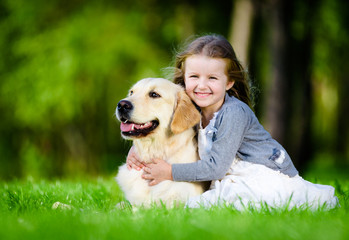 Little girl sitting on the green grass with labrador