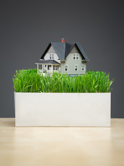 Close up of house model with green grass on grey background.