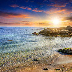 calm sea with waves on  sandy beach at sunset