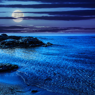 calm sea with waves on  sandy beach at night
