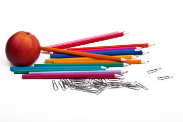 Цветные карандаши, яблоко, скрепки на белом фоне