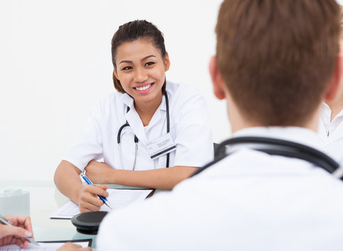 Doctor Looking At Colleague In Meeting