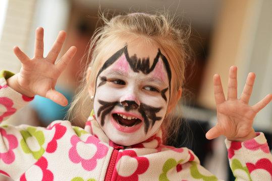 enfant avec son visage peint en étant