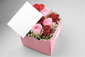 Blank greeting card over decorative box of roses