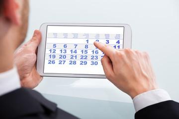 Fototapete - Businessman Touching Calendar Date On Digital Tablet In Office