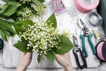 Poster de jardin Muguet de mai Florist at work. Woman making bouquet of lily of the valley flow