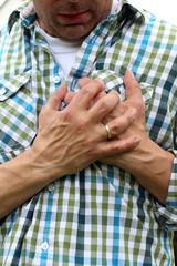 Mann schaut und fasst sich an Brust Herzattacke