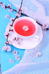 Fragrant tea with flowering branches on wooden table close-up