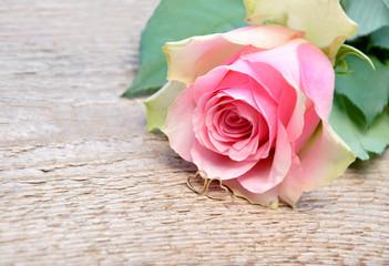 Rose mit zwei kleinen goldenen Herzchen
