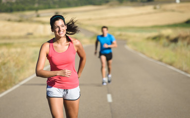 Woman and man running in country road