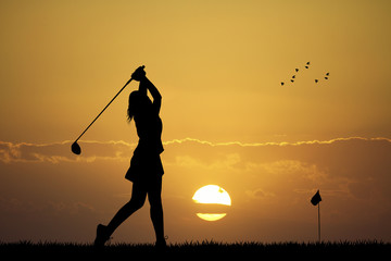 woman playing golf at sunset