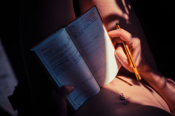 Naked woman writing in notebook