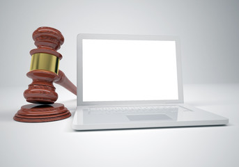 Gavel and open white laptop