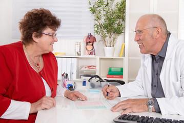 Besprechung beim Arzt: Doktor mit Seniorin