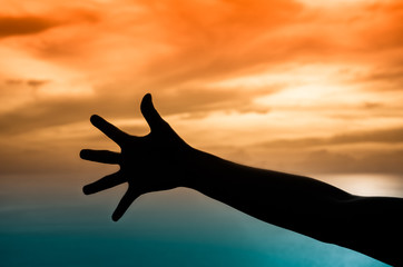 Hand silhouette under a sunset backdrop.